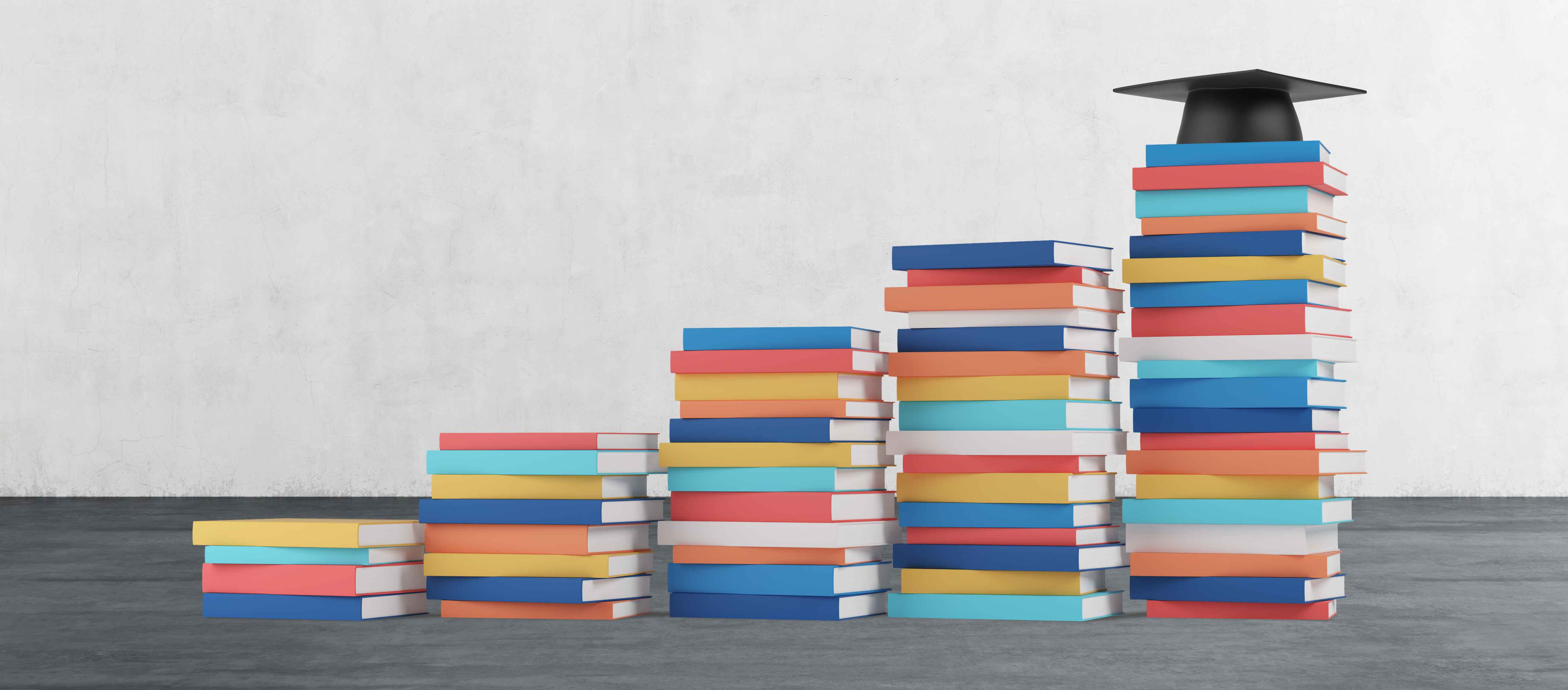 Stacks of college textbooks arranged in a stairway to a graduation cap